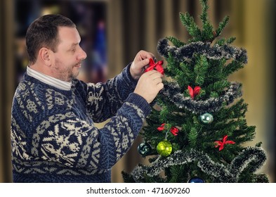 Standing sideways middle-aged man hangs red bow on Christmas tree with pleasure. Bearded man wears Scandinavian sweater. Half body portrait. Horizontal shot on blurry indoors background