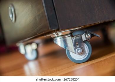 Standing small metal furniture wheel on wooden  floor