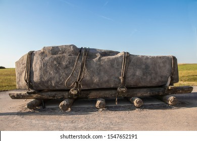 Standing stone horizontal on sledge with rollers  tied down with ropes like the stones at Stonehenge may have been moved