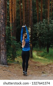 Standing stretch arms up. Girl in blue sportswear doing exercises outdoors in coniferous forest. Healthy lifestyle sport concept