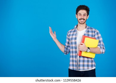 Standing student holds two books inviting, pointing with one hand with a smile, on a blue background.