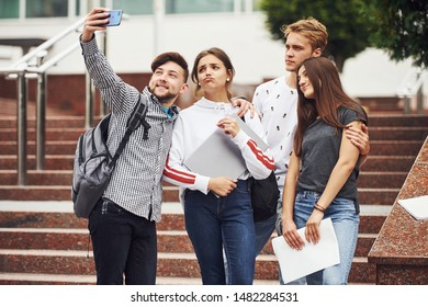 Standing and taking selfie. Group of young students in casual clothes near university at daytime.
