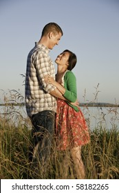 Standing in tall grass is a mixed race couple arm in arm.