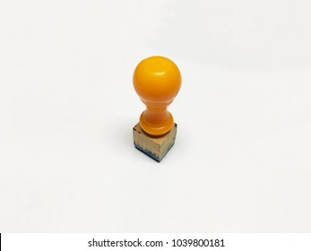 Standing used yellow wood rubber stamper with white isolated background.