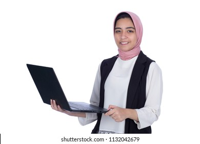 Standing veiled girl holds laptop smiling wearing pink scarf, isolated on a white background.