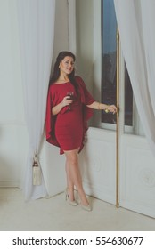 standing at the window of wine a beautiful girl in a red dress