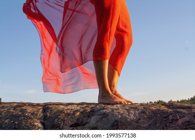 Standing woman beautifull legs posing upon the wall, wearing a pareo against the summer blue sky