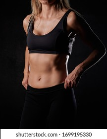 Standing woman in black sportwear with the hands on waist, belly closeup, black background