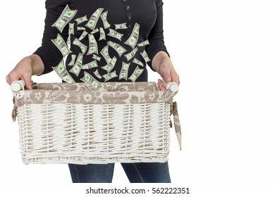 Standing woman is holding white basket, where falling US dollar bills. All is isolated on the white background.