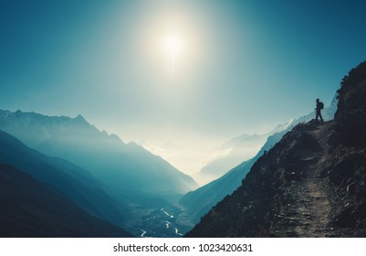 Standing woman on the hill against mountain valley at bright sunny day. Landscape with girl, trail, mountain, blue sky with sun and low clouds at sunset in Nepal.  Lifestyle, travel. Trekking