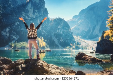 Standing woman on the stone with raised up arms on the coast of Braies lake at sunrise. Autumn in Dolomites, Italy. Landscape with happy girl, mountains, water with reflection, fall trees and blue sky