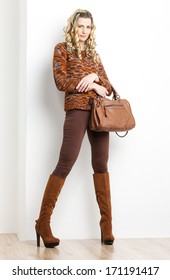 standing woman wearing brown clothes and boots with a handbag