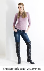 standing woman wearing jeans and black boots