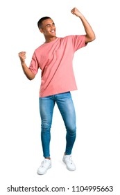 Standing young african american man celebrating a victory in winner position on isolated white background