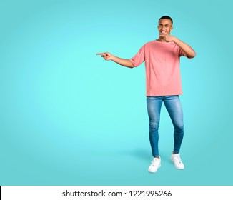 Standing young african american man pointing finger to the side and presenting a product while smiling on colorful background