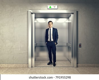 standing young businessman in modern elevator