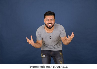 Standing young man bending forward raises hands saying surprise on navy blue background.