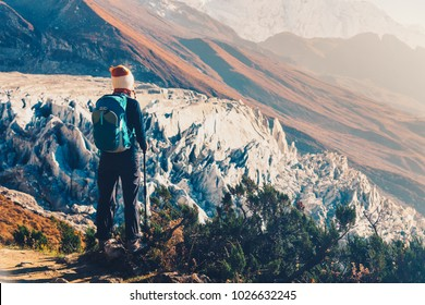Standing young woman with backpack on the mountain peak against beautiful mountains and glacier at sunset. Landscape with girl, rocks with snowy peaks at bright sunny day in Nepal. Travel.Trekking