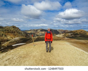Standing young woman with backpack on the mountain peak looking on beautiful rhyolite rainbow mountains at summer. Landscape with girl, colorful mountain hills, Laugavegur hiking trail, Iceland