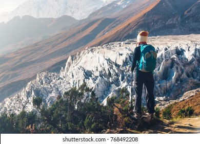 Standing young woman with backpack on the mountain peak and looking on beautiful mountains and glacier at sunset. Landscape with girl, rocks with snowy peaks,blue sky in Nepal.Hiking, travel.Trekking