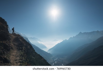 Standing young woman on the hill and looking on mountain valley. Landscape with girl, path, mountain, blue sky with sun and low clouds at sunrise in Nepal.  Lifestyle, travel. Trekking in Himalayas.