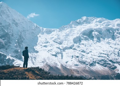 Standing young woman on the mountain trail and looking on snow covered rocks at sunset. Landscape with girl, high mountains with snowy peaks, path, blue sky in Nepal. Travel. Vintage style. Nature
