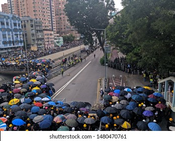 A standoff between riot police and protesters with umbrella and helmet at Yuen Long during a protest in Hong Kong