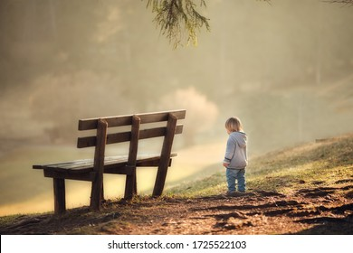A сhild stands near a bench on a mountain hill at spring sunset on blurried background