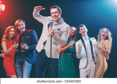 Stand-up comedy and party. Showman with microphone. Group of cheerful friends toasting with wineglasses among confetti.