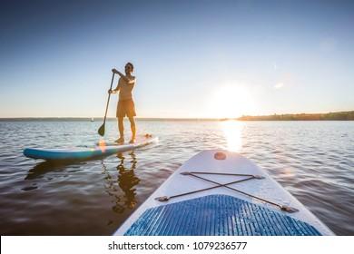Standup-Paddler bei Sonnenuntergang am See