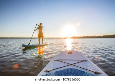 Standup paddler at the lake during sunset
