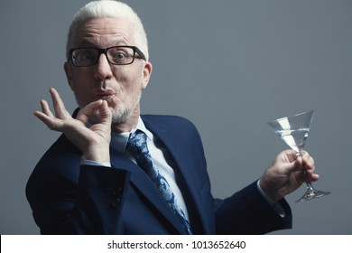 Stand-up party concept. Funny businessman with silver hair in expensive blue costume and trendy eyewear holding glass and showing OK. Close up. Text space. Studio shot
