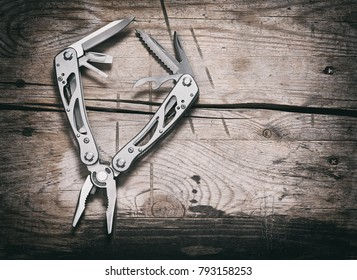 stanless steel multitool on wooden background top view