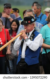 Stans, Canton Nidwalden / Switzerland - August 01 2014: Event for the Rollout of the new Jet PC-24 from Pilatus Aircraft at Swiss National Day - a group of alphorn (alpenhorn) players