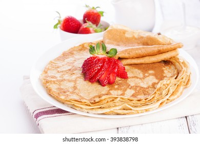 Staple of wheat golden yeast pancakes or crepes, with fresh strawberry on a wooden table on a white background closeup