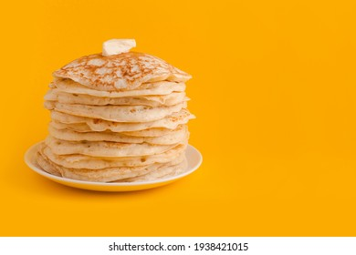 Staple of yeast pancakes with butter. Spring holiday Traditional Russian pancake week. isolated on yellow background