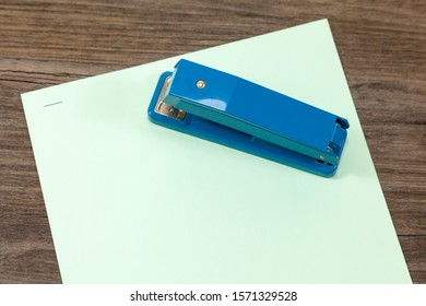 Stapled paper with blue stapler on top
