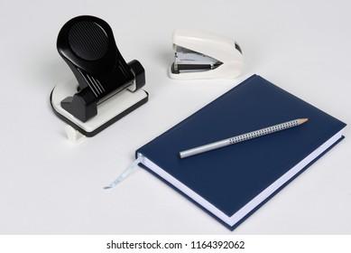 stapler, puncher, datebook, pencil lying on white background