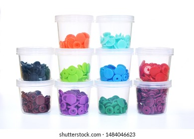 Staples of colorful plastic snap fastener buttons in transparent containers on white background