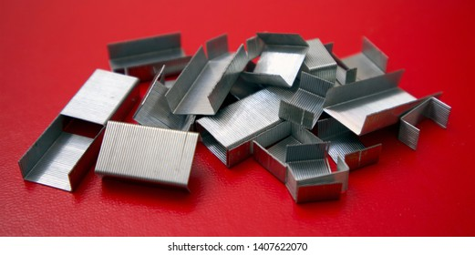 Staples from a stapler machine laid on a red background.  Office staples in silver colour on a red book, different lengths of staple cartridges.