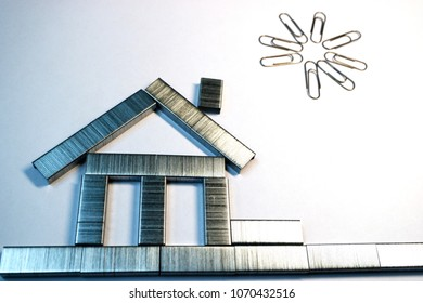 from the staples from the stapler is made a house on white paper, over the house of paper clips, the sun