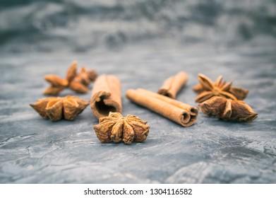 Star anis and cinnamon sticks on vintage dark background. Selective focus
