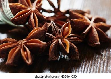Star anise, glass jar of dark wood table