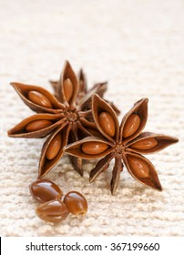 Star Anise and seeds place in groups of three shot vertically with selective focus on a cream textured background.