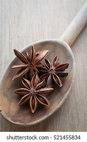 Star Anise spice pods on a wooden kitchen spoon.