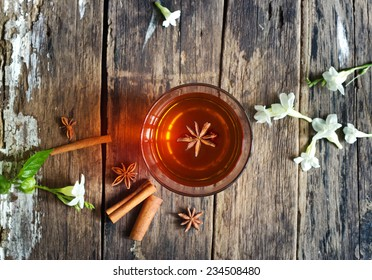 star anise in tea glass vibrant top view on wooden and cinnamon background