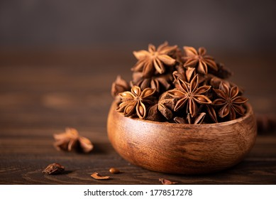 star anise in a wooden bowl on the table, close up