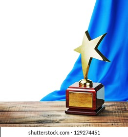 Star award wooden table and on the background of blue curtain with space for text