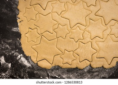 Star cookies cut out of the dough, preparation before baking.