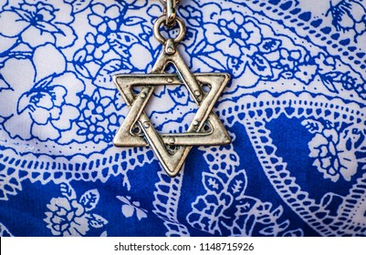 A Star of David, famous Jewish hexagram symbol, on a blue and white background.